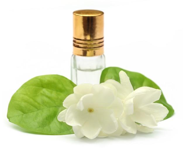 Flor de jasmim com frasco de essência sobre fundo branco