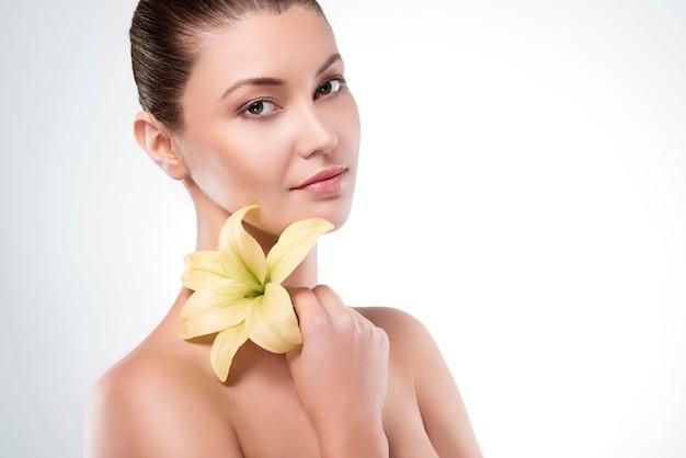 Flor de lírio segurada por uma mulher atraente