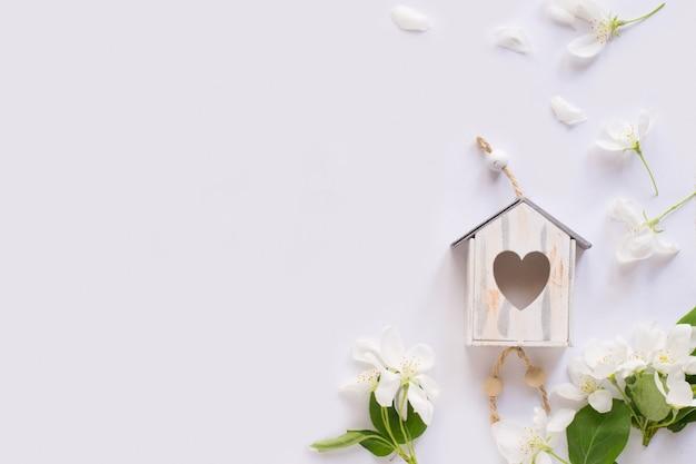 Flor de maçã, casa de passarinho em fundo branco