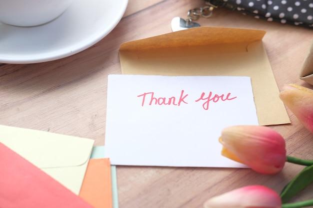 Flor de mensagem de agradecimento e envelope na mesa de madeira