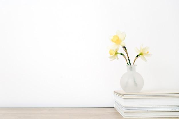 Flor de narciso amarelo pálido lindo em vaso na mesa em frente ao branco. composição floral