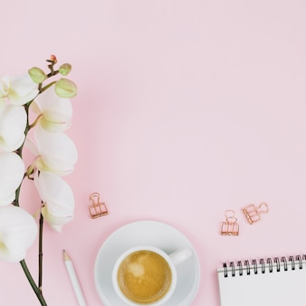 Flor de orquídea branca linda macia; lápis; xícara de café; grampo de papel espiral do bloco de notas e do buldogue contra o fundo cor-de-rosa