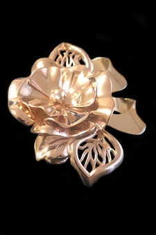 Flor de ouro sobre fundo preto. broche de ouro em forma de flor, isolado em um fundo preto. decoração dourada, tema de primavera