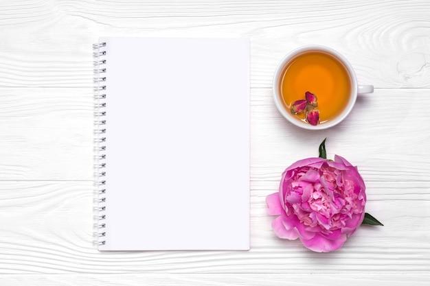 Flor de peônia, caderno com lugar para texto, xícara com chá de botão de rosa em fundo branco de madeira.