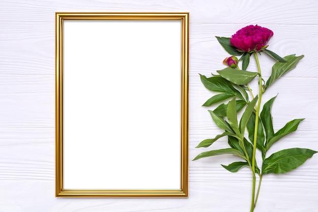 Flor de peônia e uma moldura de ouro sobre fundo branco de madeira.