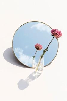 Flor de peônia rosa seca em um vaso transparente refletida em um espelho