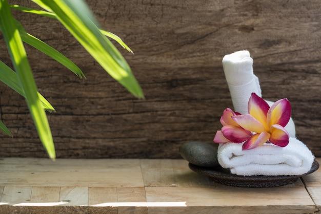 Flor de plumeria e bola de massagem para produtos de aromaterapia em madeira