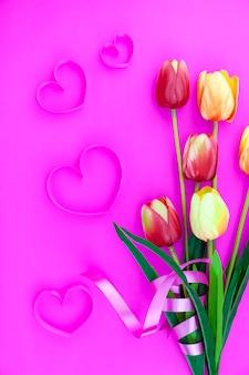 Flor de primavera de multi cor tulipas no fundo rosa, flat leigos imagem para cartões de férias para o dia da mãe, dia dos namorados, dia da mulher e espaço de cópia de espaço para seu texto