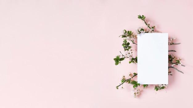 Flor de primavera e cartão branco em branco sobre fundo de pêssego imagem simulada