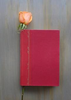Flor de rosa e capa dura vermelha no fundo de madeira.
