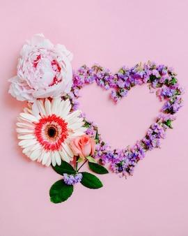 Flor de rosa, gerbera e peônia com forma de coração no fundo rosa