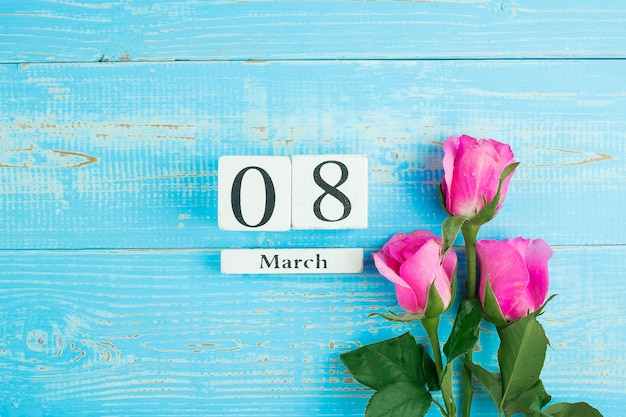 Flor de rosa rosa e 8 de março calendário sobre fundo azul mesa de madeira com espaço de cópia de texto. conceito de dia internacional do amor, igualdade e mulheres