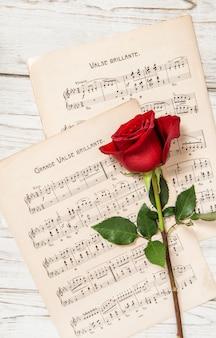 Flor de rosa vermelha na folha de notas musicais