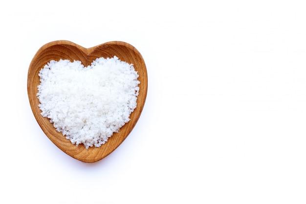 Flor de sal no coração em forma de tigela de madeira em branco