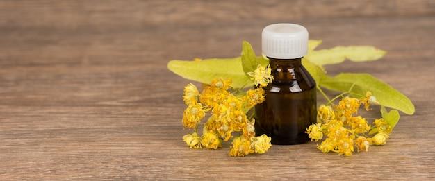 Flor de tília com frasco de vidro marrom escuro. medicina alternativa ou conceito de cura popular.