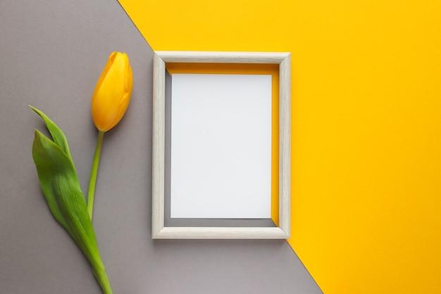Flor de tulipa amarela e papel vazio com moldura de madeira em fundo amarelo e cinza geométrico.