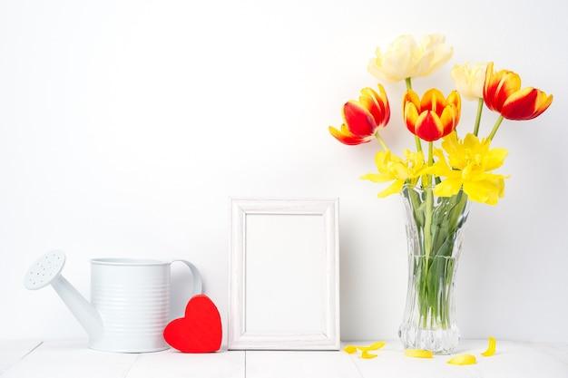 Flor de tulipa em um vaso de vidro com moldura para retrato no fundo da mesa de madeira branca contra a parede limpa em casa, close-up, conceito de decoração do dia das mães.