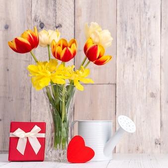 Flor de tulipa em vaso de vidro sobre a parede de fundo de mesa de madeira para o conceito de design do dia das mães.
