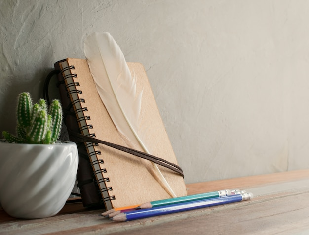 Flor do cacto com o caderno no conceito interior moderno do fundo da tabela de madeira.