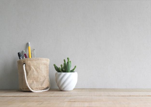 Flor do cacto com pena e lápis na cesta do suporte na tabela de madeira.