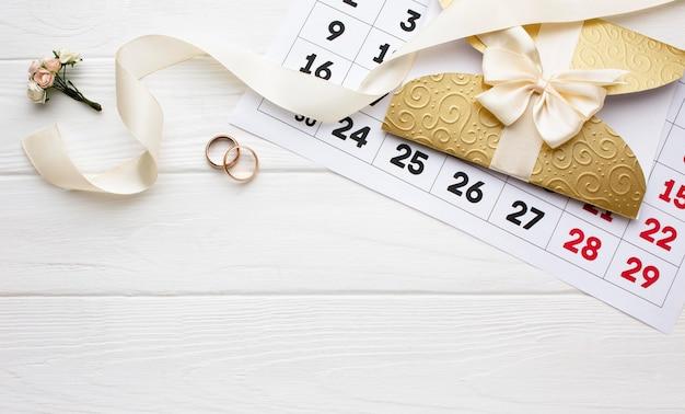 Flor e alianças de casamento com calendário
