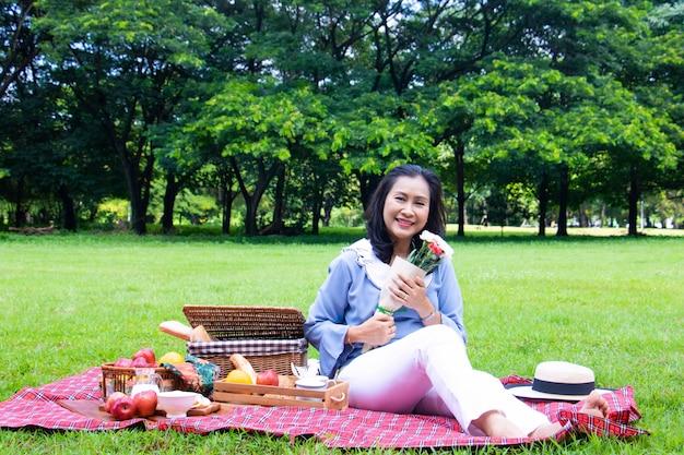 Flor e mulher no parque. ela está segurando lindo buquê de flores