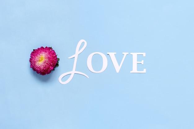 Flor e palavra amor em uma vista superior de fundo azul claro