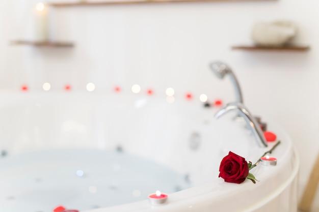 Flor e velas nas bordas da banheira de hidromassagem