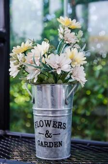 Flor em panela de alumínio nas prateleiras de aço pretas