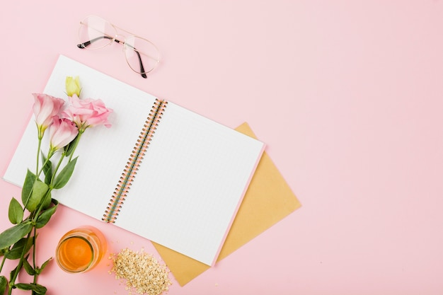 Flor em um caderno aberto; óculos; jarra de suco e muesli em fundo rosa