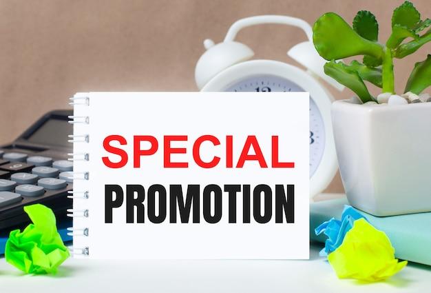 Flor em vaso, calculadora, despertador branco, folhas de papel multicoloridas e caderno branco com o texto promoção especial no desktop.