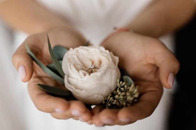Flor eustoma macia com anel de noivado com minúsculo diamante nas mãos da noiva