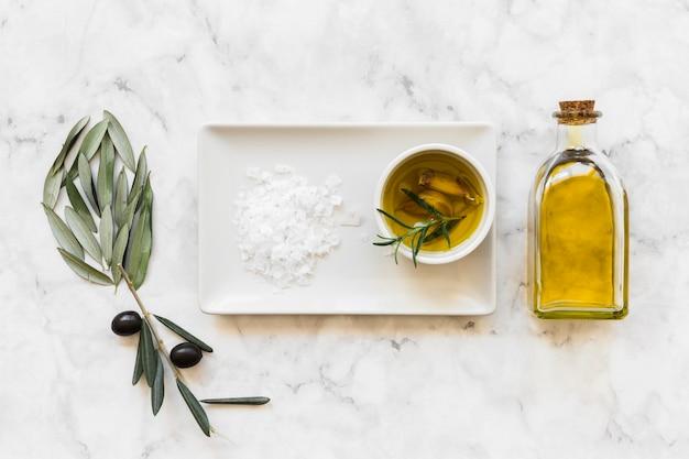 Flor feita com azeitona e folhas com sal e óleo na tigela e garrafa