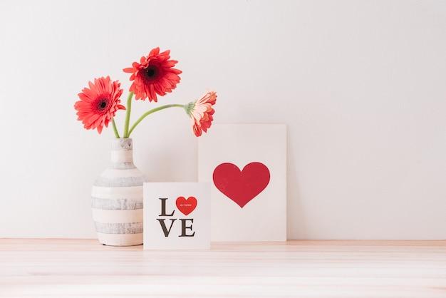 Flor gerbera em um vaso e cartão postal em forma de coração na mesa de madeira com espaço de cópia