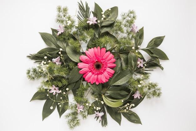 Flor gerbera rosa com ramos de plantas na mesa