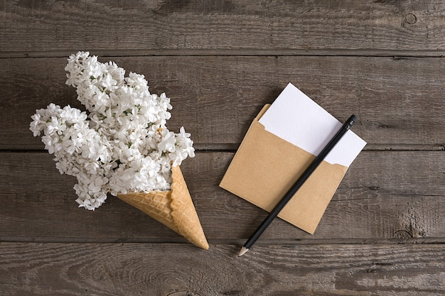 Flor lilás em fundo de madeira rústico com espaço vazio para mensagem de saudação. envelope pequeno. vista do topo. conceito de fundo de primavera.