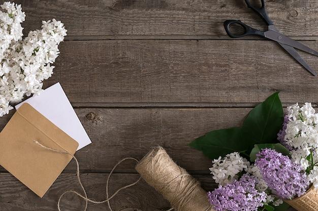 Flor lilás em fundo de madeira rústico com espaço vazio para mensagem de saudação. tesoura, carretel de linha, envelope pequeno. conceito de fundo de primavera.