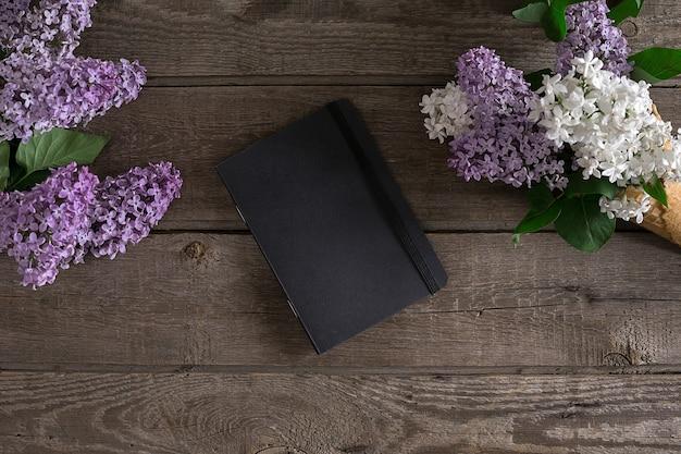 Flor lilás sobre fundo de madeira rústico com caderno para mensagem de saudação. vista do topo. conceito de fundo de primavera.