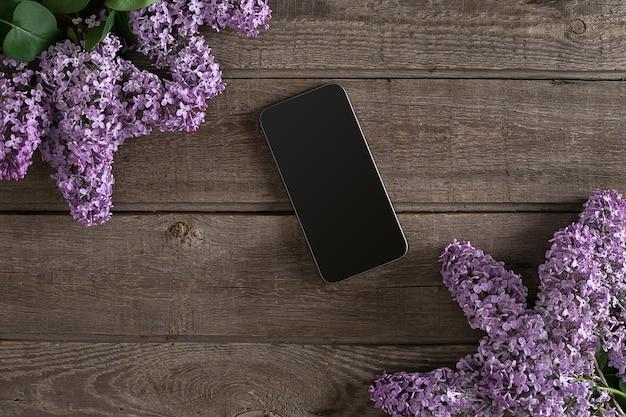 Flor lilás sobre fundo de madeira rústico, inteligente com espaço vazio para a mensagem de saudação. vista do topo. conceito de fundo de primavera.