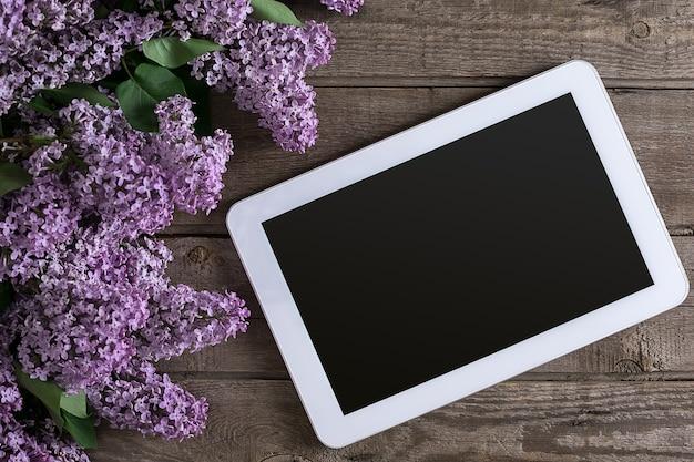 Flor lilás sobre fundo de madeira rústico, tablet com espaço vazio para mensagem de saudação. vista do topo. conceito de fundo de primavera.