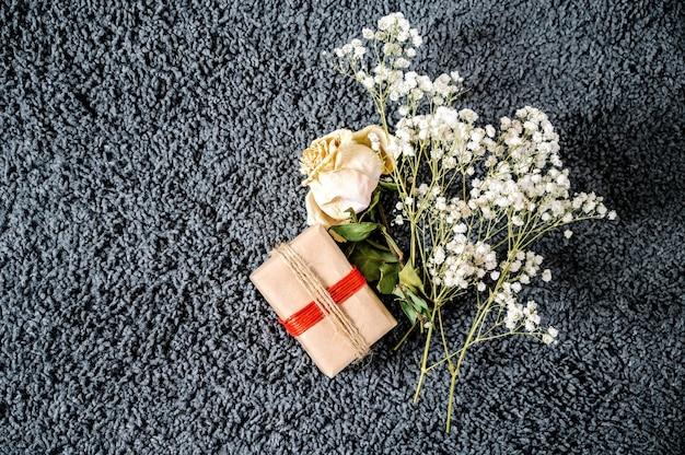 Flor murcha com corda vermelha e flores brancas