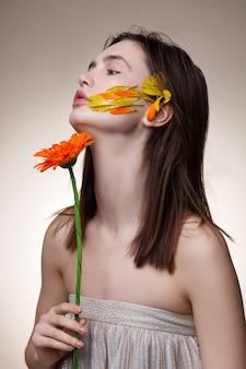 Flor nas mãos. modelo magro e atraente com cabelo escuro e liso posando com uma flor nas mãos