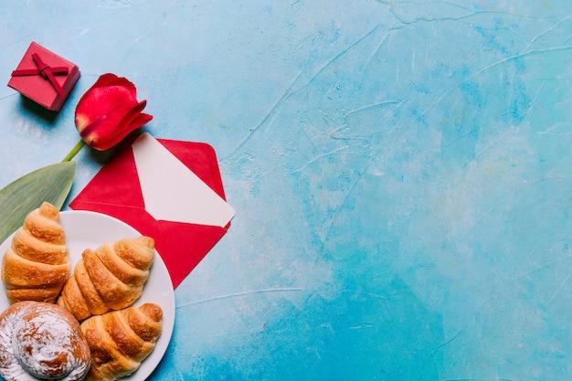 Flor, padaria no prato, caixa de presente e envelope