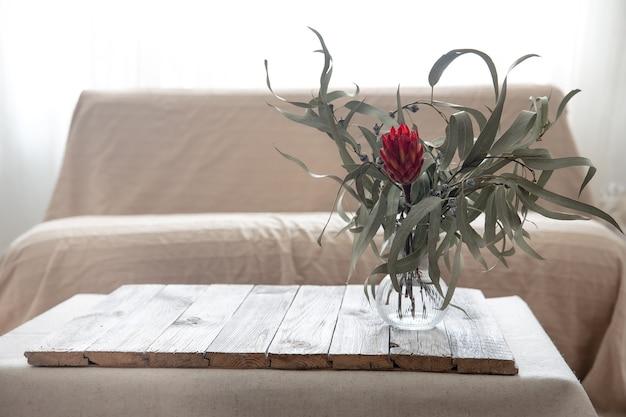 Flor protea em um vaso de vidro e um elemento de malha na mesa da sala.