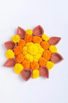 Flor rangoli para o festival diwali feita com calêndula, folha e lâmpada de óleo sobre fundo branco