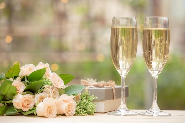 Flor rosa, caixa de presente, copo de vinho, na mesa de madeira com bokeh