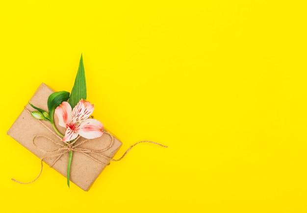 Flor rosa com caixa de presente na mesa