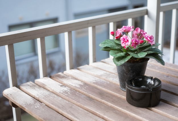 Flor rosa com cinzeiro de cerâmico na mesa de madeira no terraço