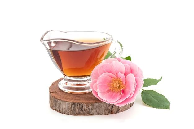 Flor rosa do damasco e chá isolado no fundo branco.