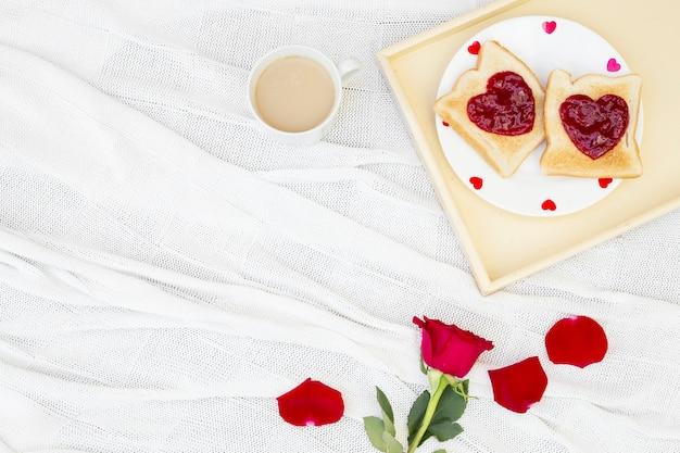 Flor rosa e torradas no café da manhã